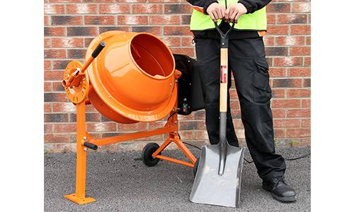 Man Stood Next To Cement Mixer With Spade